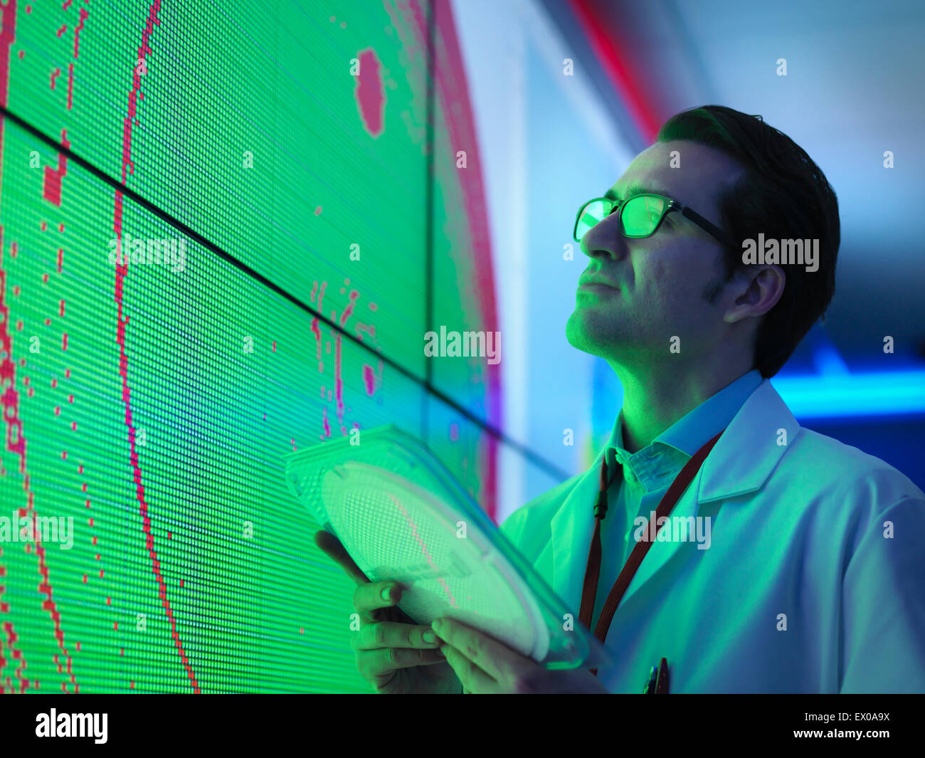 Male scientist with silicon wafer studying graphical display of wafer on screens - Stock Image