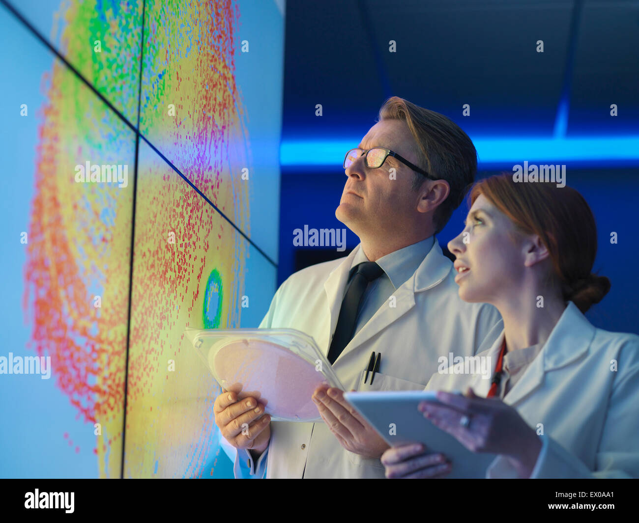 Scientists with silicon wafer studying graphical display of wafer on screens - Stock Image
