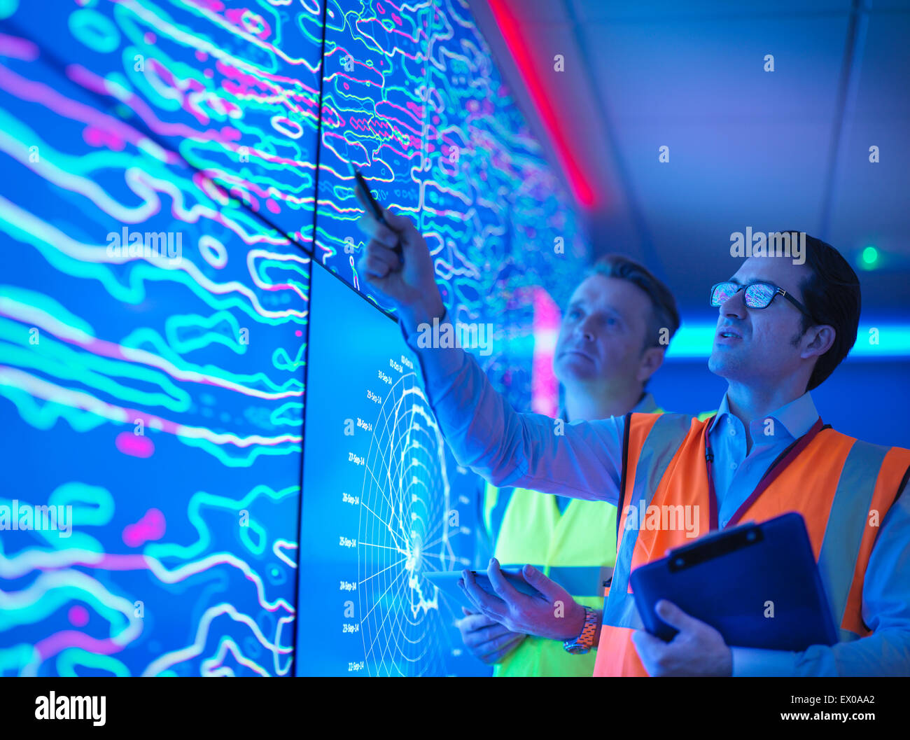 Geologists studying graphical display of oil and gas bearing rock on screens - Stock Image