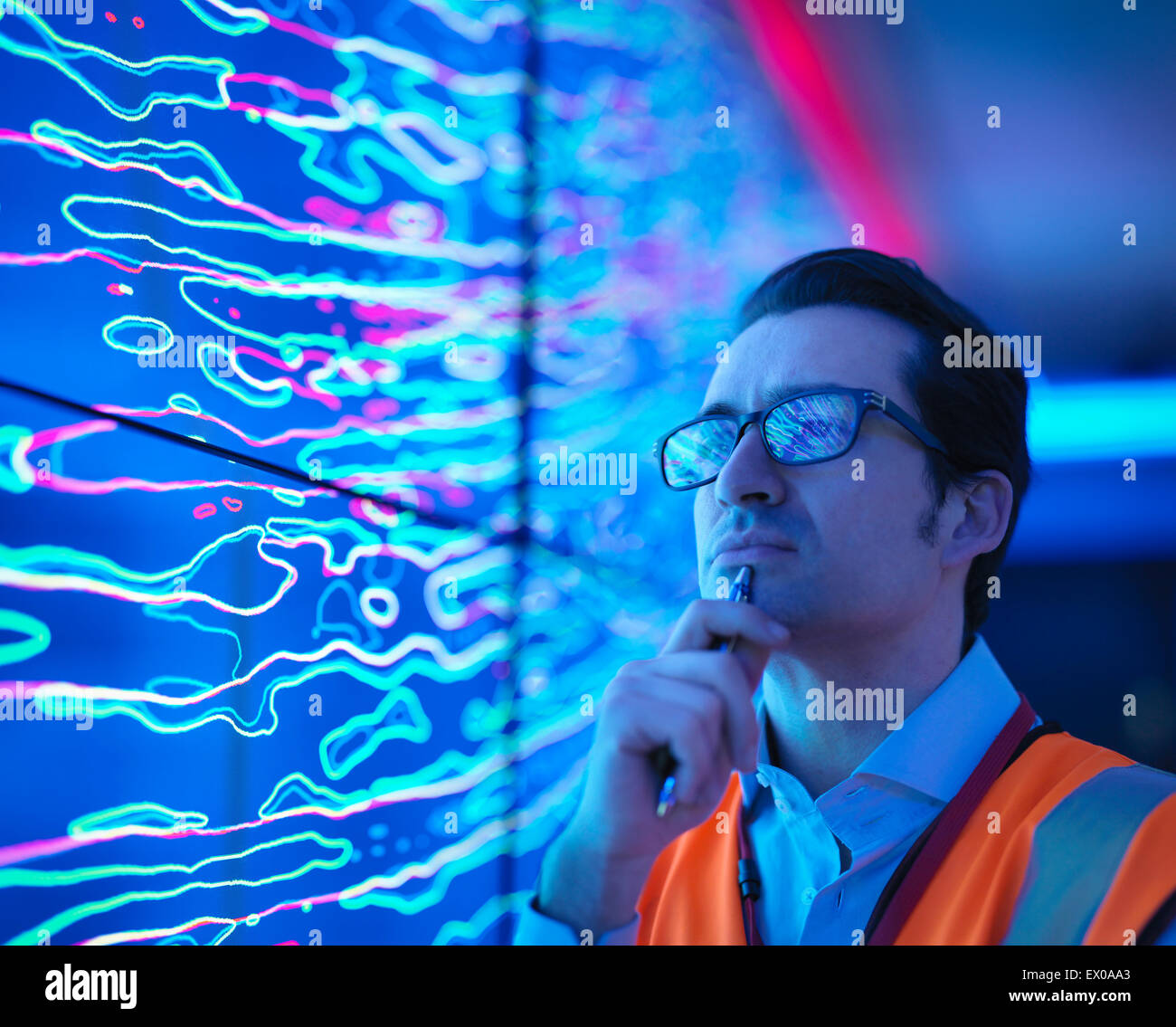 Geologist studying graphical display of oil and gas bearing rock on screens, close up - Stock Image
