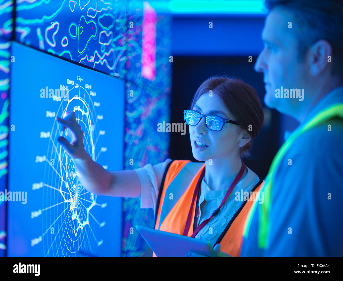 Female geologist with colleague studying graphical display of oil and gas bearing rock on screens - Stock Image