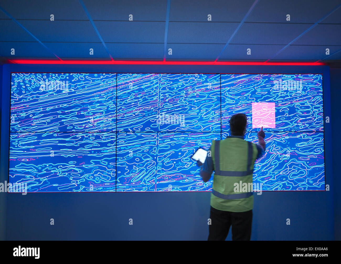 Geologist studying graphical display of oil and gas bearing rock on screens - Stock Image