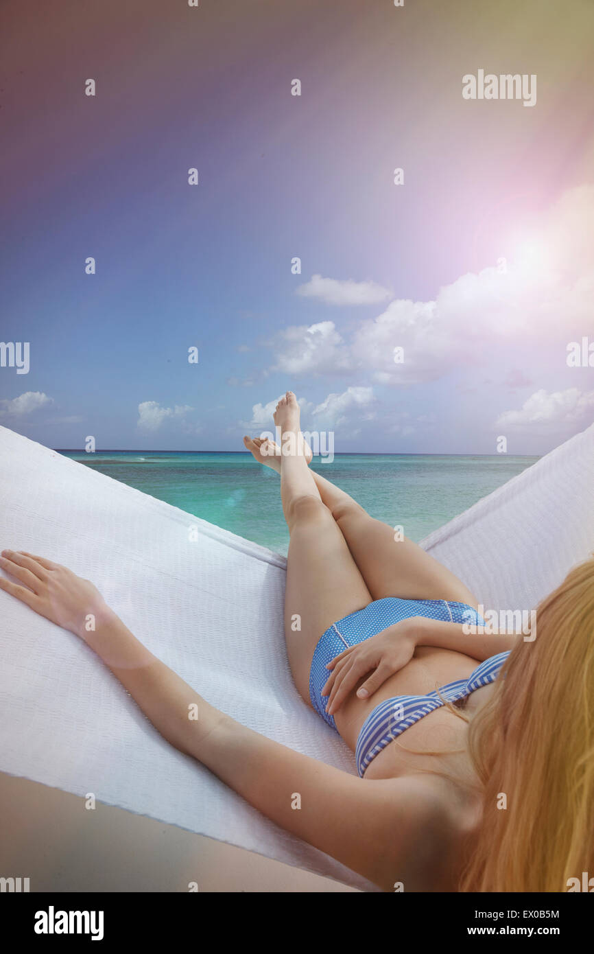 Over the shoulder view of young woman reclining on hammock on Miami Beach, Florida, USA - Stock Image