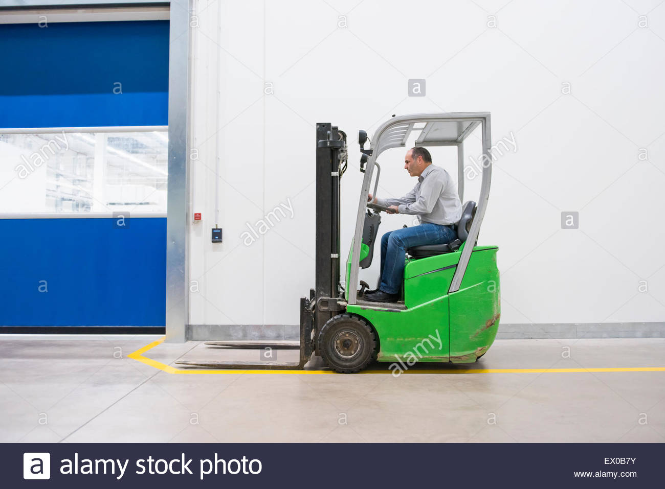 Man driving forklift truck in factory corridor - Stock Image