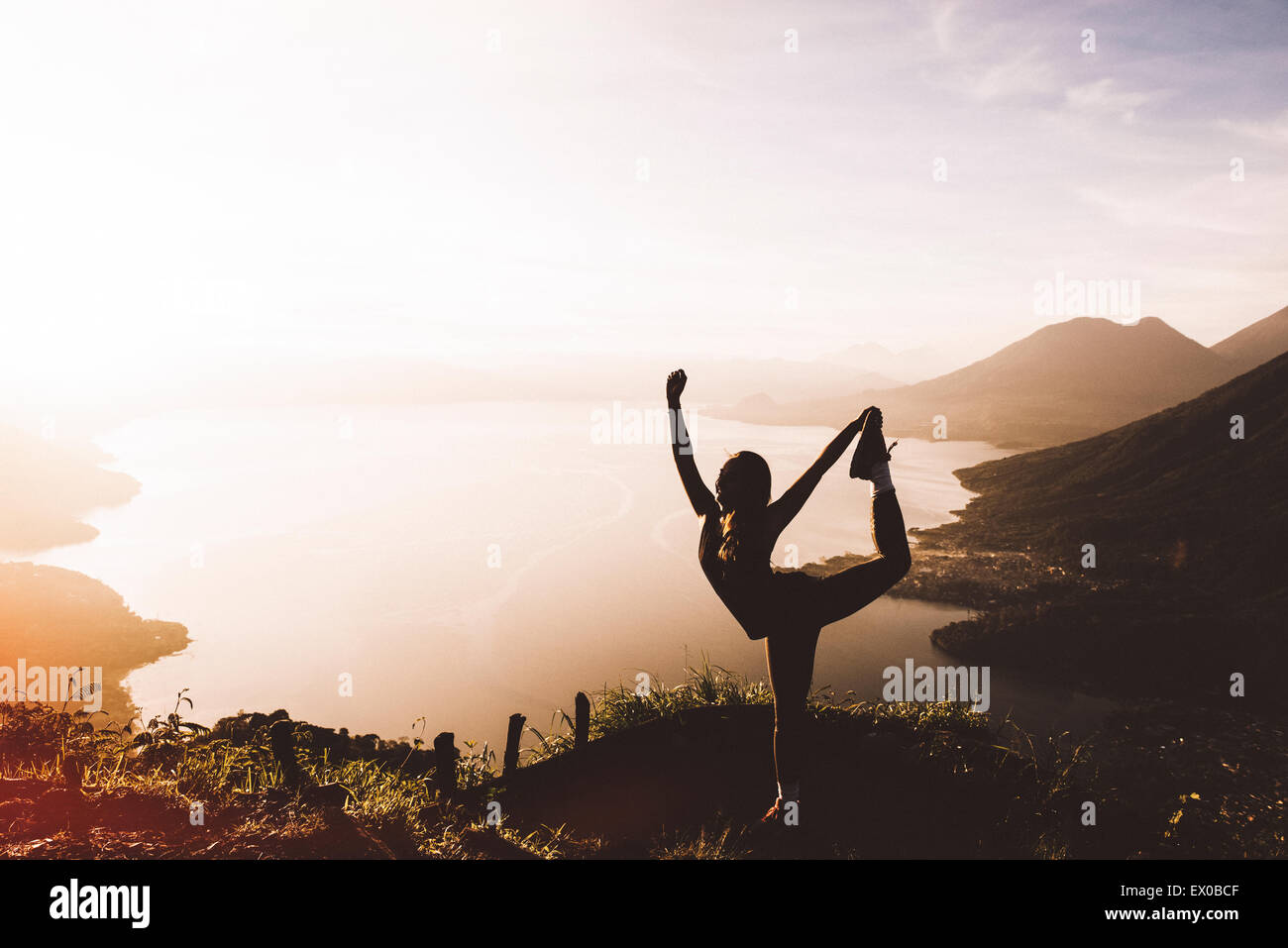 Silhouetted view of young woman posing at sunset above Lake Atitlan, Guatemala - Stock Image