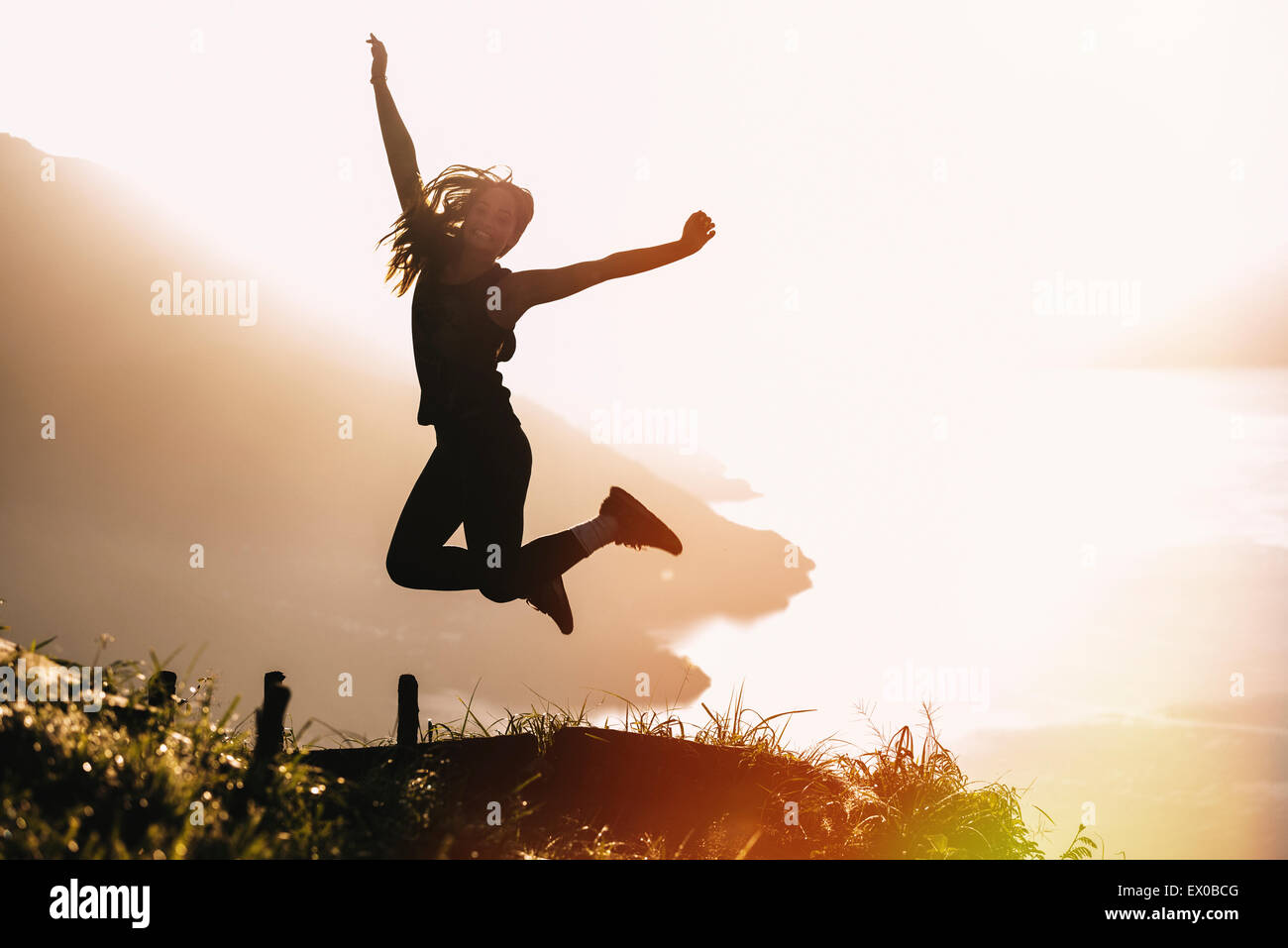 Silhouetted view of young woman jumping mid air at sunset above Lake Atitlan, Guatemala - Stock Image