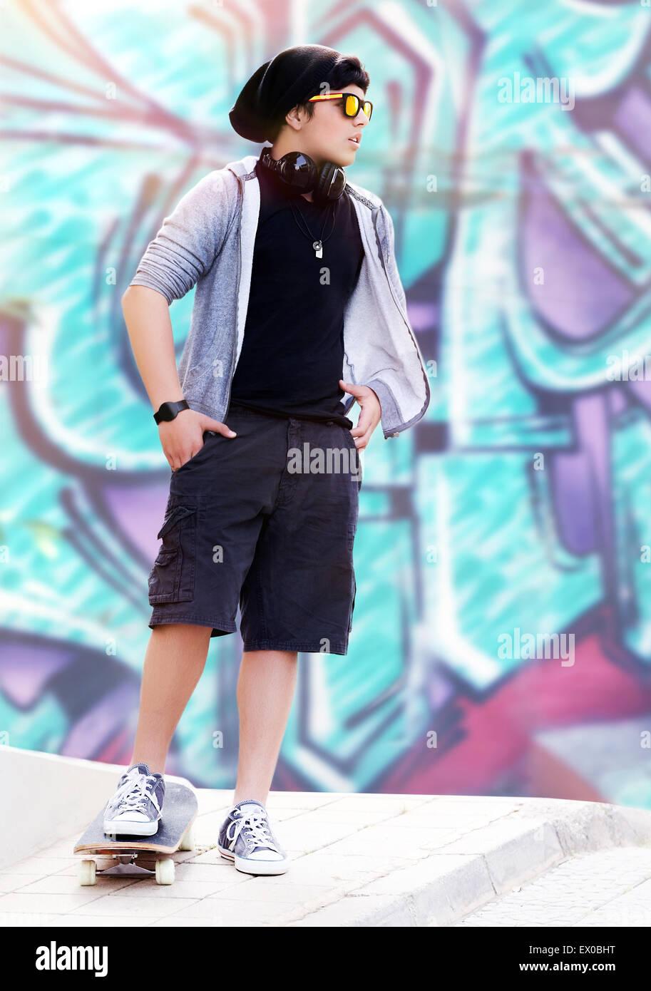 49d708398ea Stylish skater boy listening music standing outdoors on beautiful graffiti  wall background