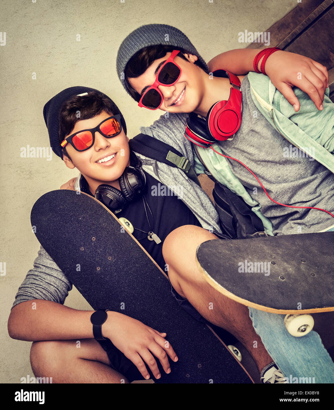 Two happy stylish teen boys sitting on the bench and holding skateboards, cheerful active friends enjoying outdoors - Stock Image