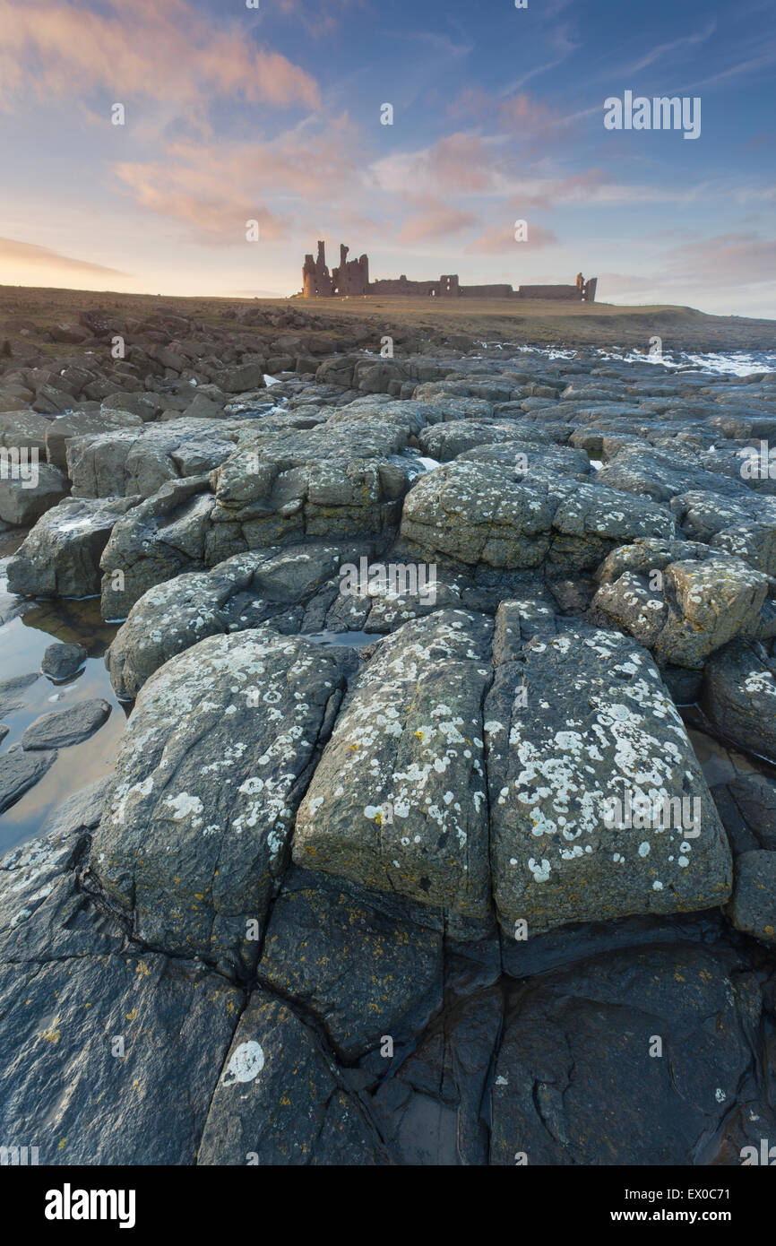Dunstanburgh Castle shot from the rocky foreshore at sunset, Craster, Northumberland, UK - Stock Image