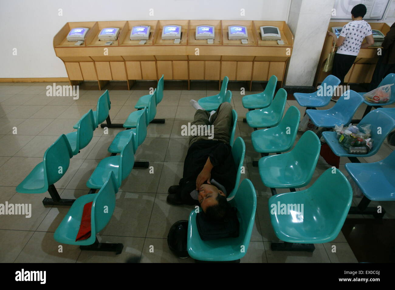 An investor naps in front of an electronic board with stock information at a brokerage house in Wuhan, Hubei province - Stock Image