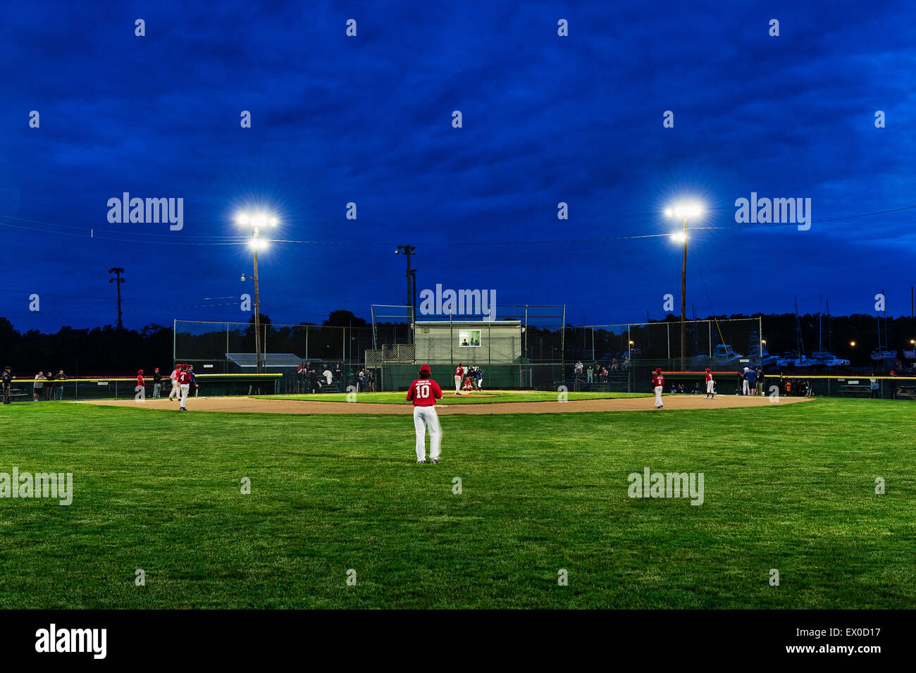 Little League baseball game at night. - Stock Image