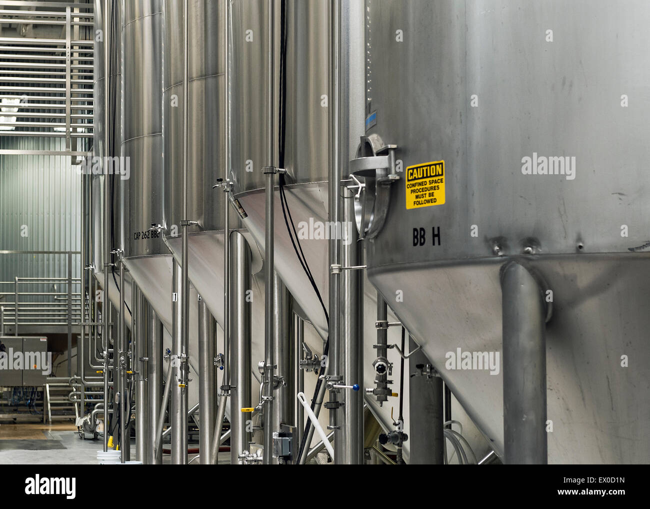 Fermentation tanks at a brewery. - Stock Image