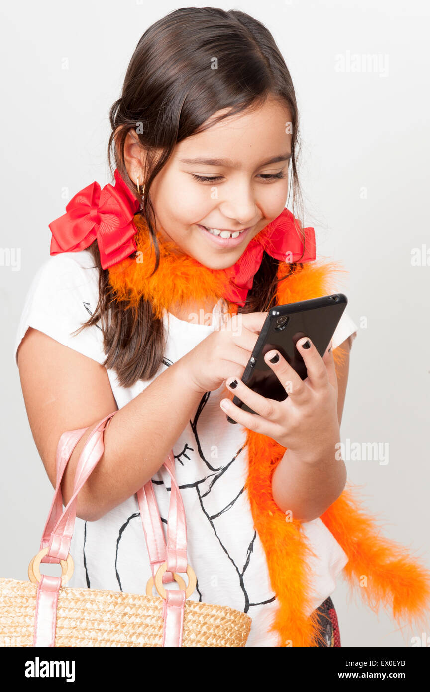 Cute young girl smilling, indoor photo using mobile phone. - Stock Image