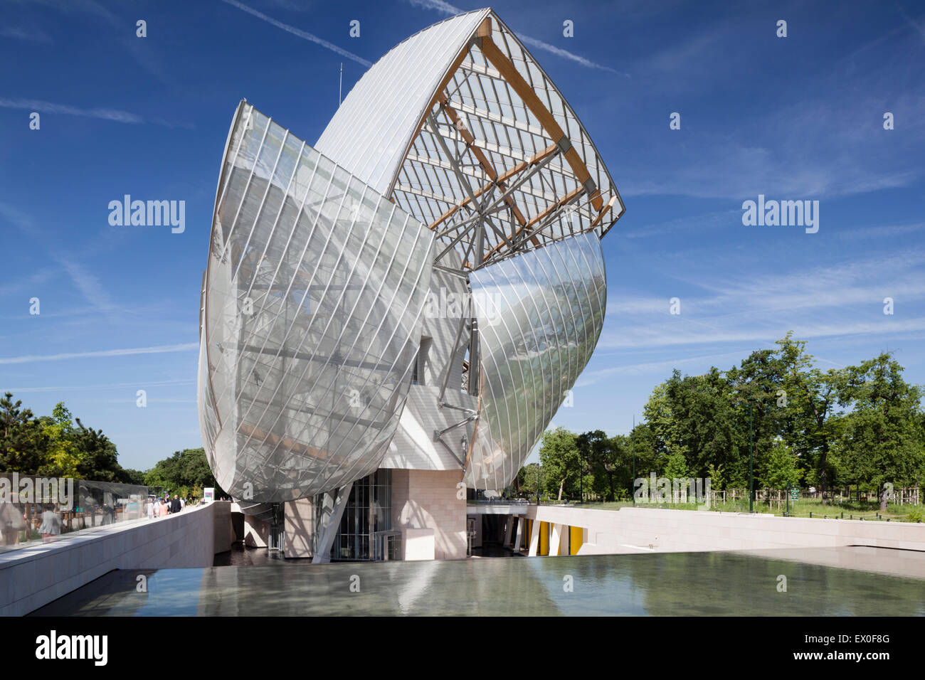 Fondation Louis Vuitton, Bois de Boulogne, Paris, France. East facade view of a water feature in front of the sail - Stock Image