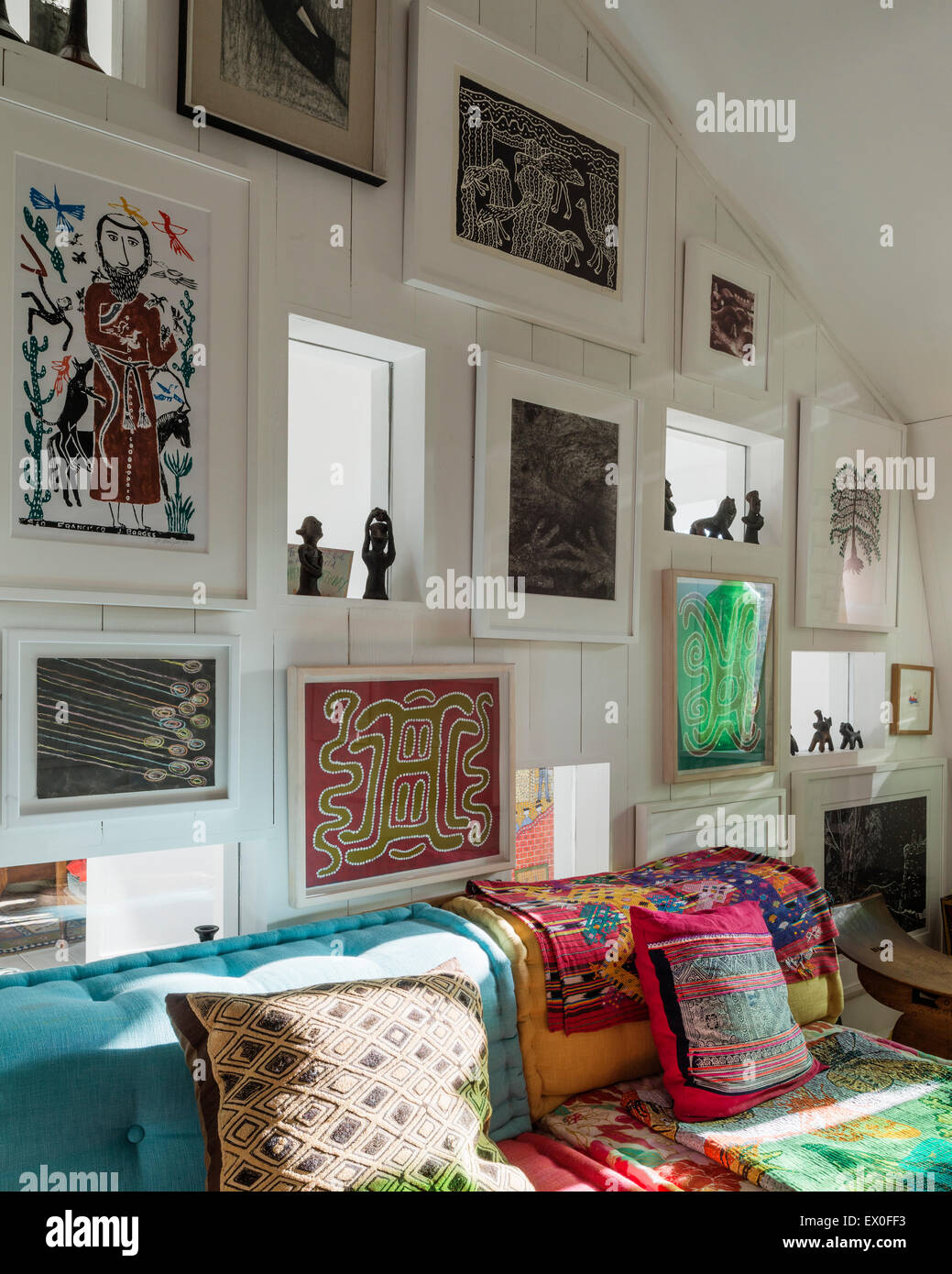 Assorted art on wall including work by J Borges and J Pike above blue buttoned sofa with Guatemalan textiles - Stock Image
