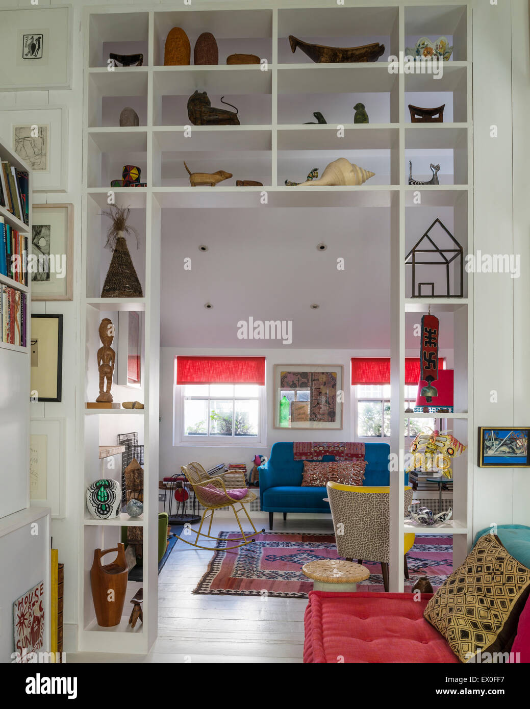 Small sculptures and artefacts on open shelving in living room with bold coloured furniture and kilim - Stock Image