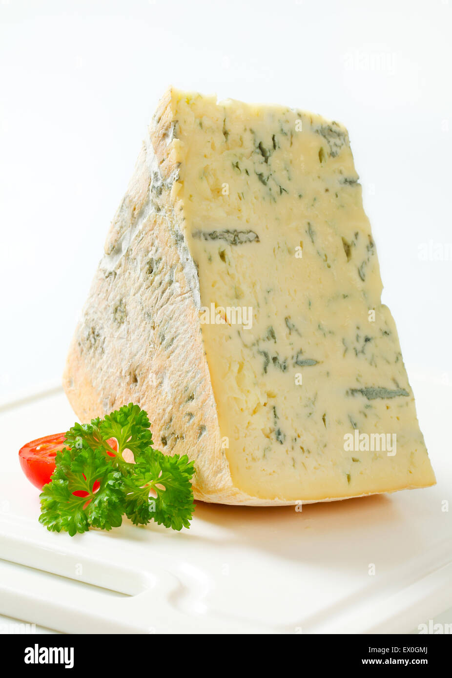 Large wedge of blue cheese on a cutting board - Stock Image