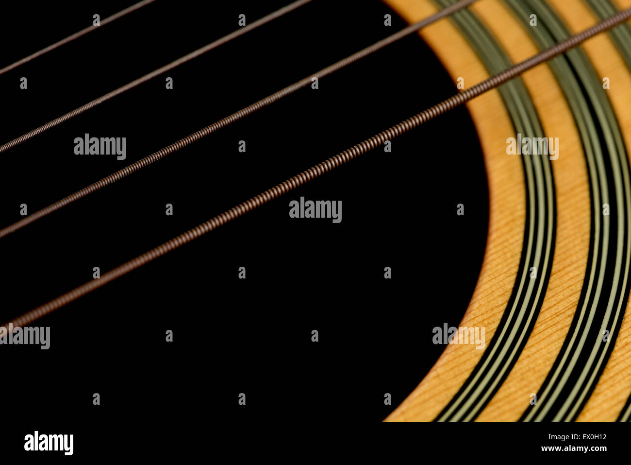 An angled macro shot of acoustic guitar strings and the wood around the sound hole of the guitar. - Stock Image