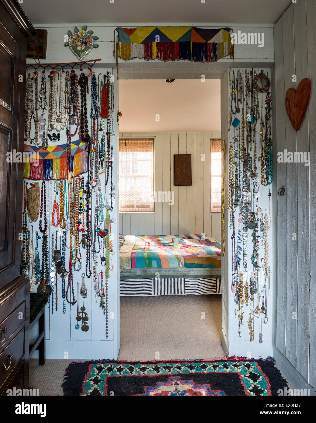 Necklaces hung from pins around doorway into bedroom - Stock Image