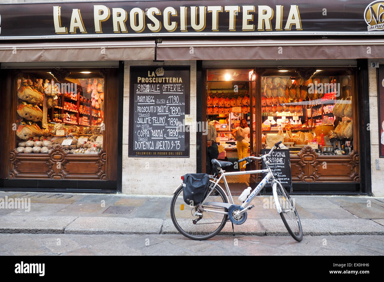 A bicycle parked outside a prosciutteria store, where Parma ham can be bought. - Stock Image