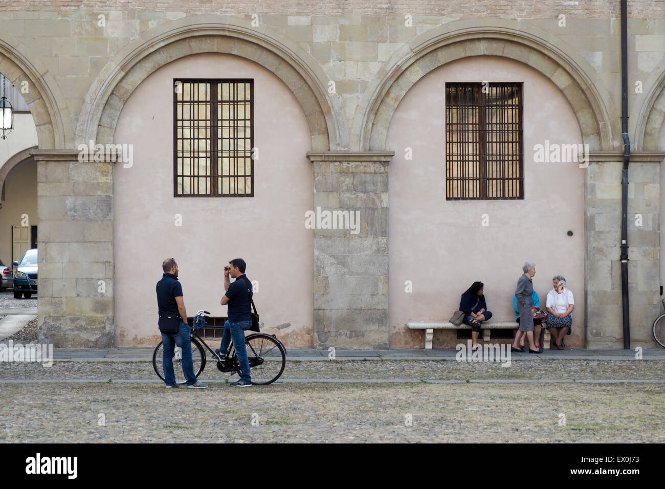 Elderly ladies sitting on a bench and two men talking. - Stock Image