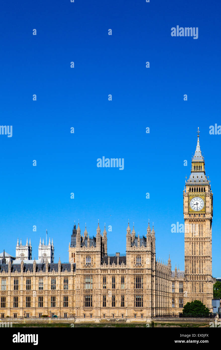 A view of the magnificent architecture of the Palace of Westminster in London. The towers of Westminster Abbey can - Stock Image