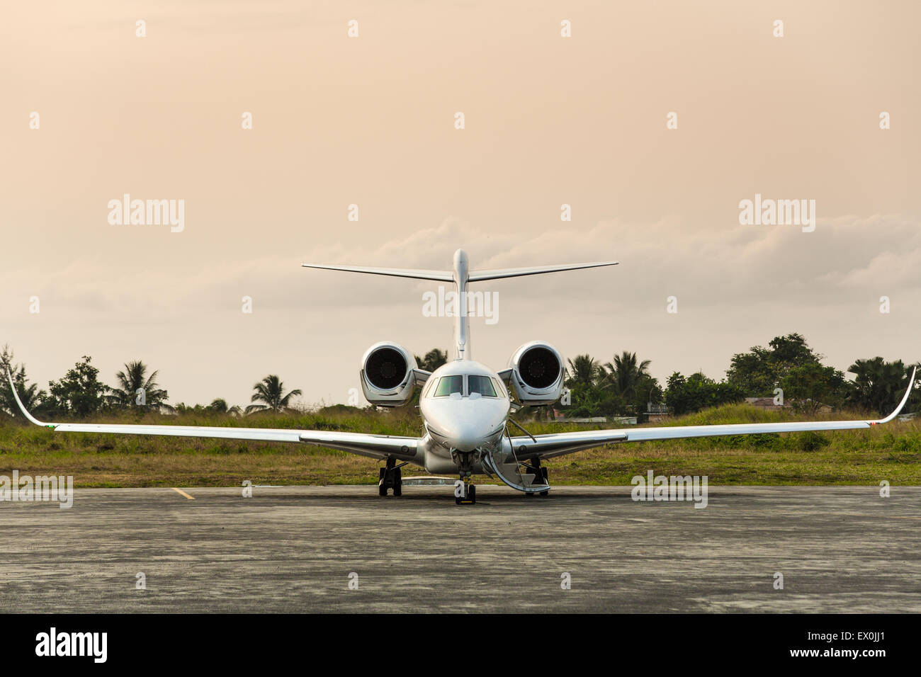 Private jet sits on the runway on a tropical island - Stock Image