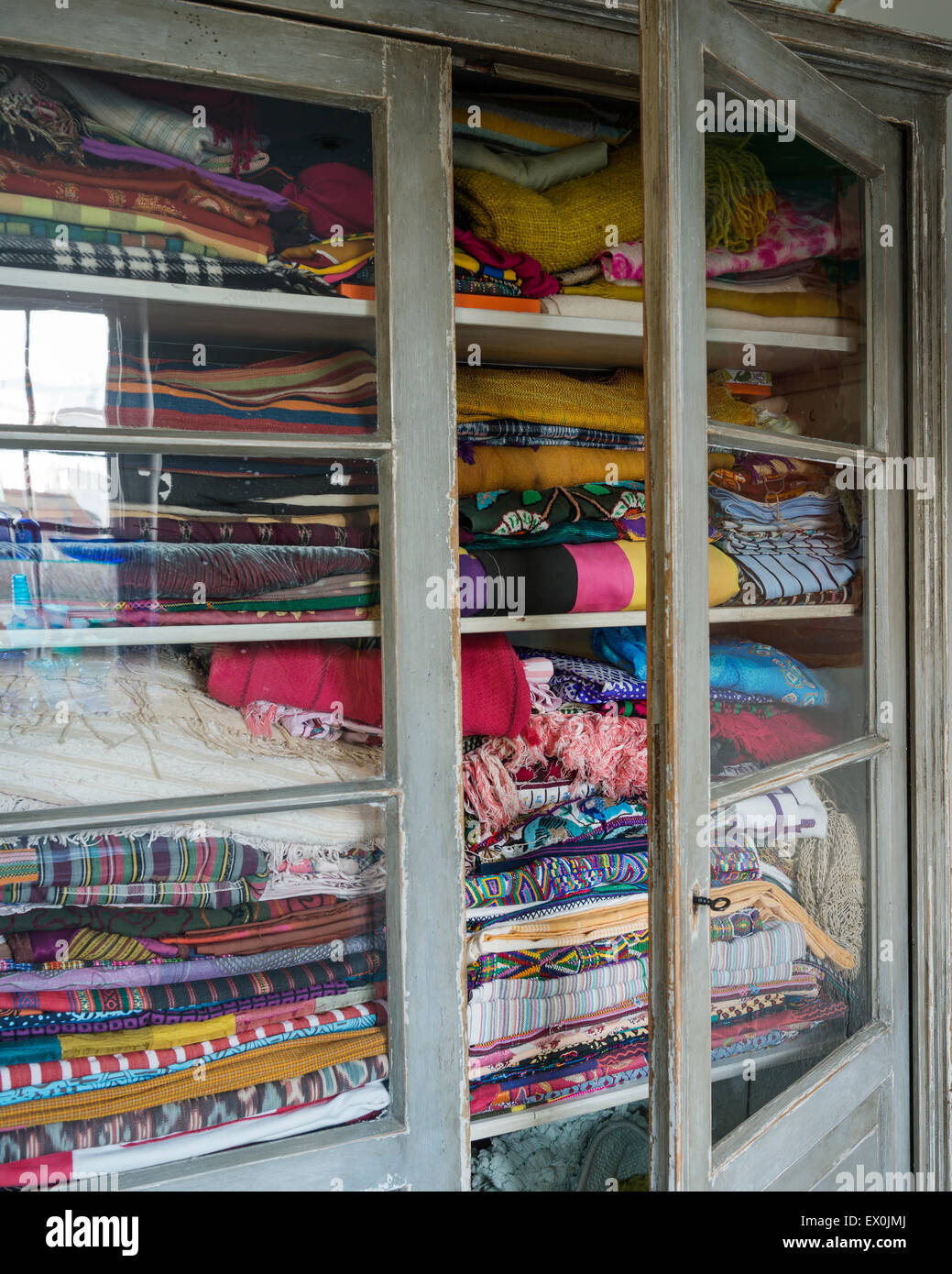 Glass fronted cabinet full of assorted fabrics and textiles from across the world - Stock Image