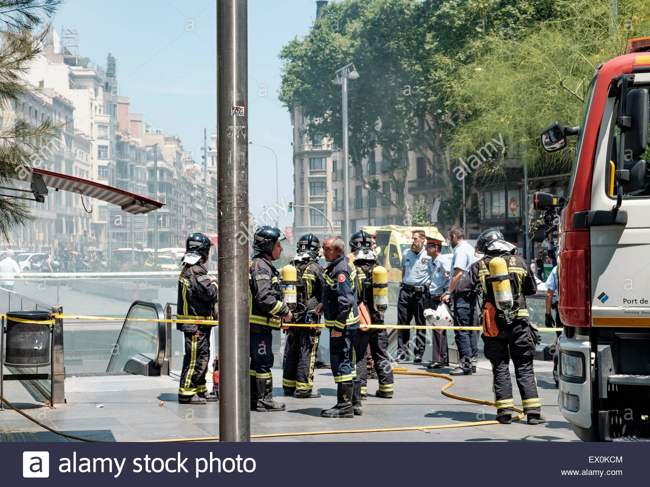 Firemen standing at the entrance to Universitat station on the Barcelona Metro during a fire - Stock Image