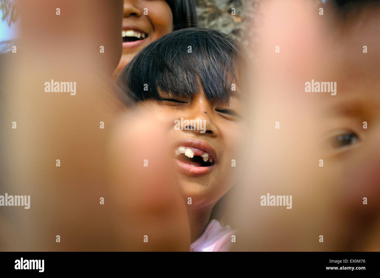 Street children scramble forward to the front of the lens when about to be photographed in Pondok Kelapa Cemetery, - Stock Image