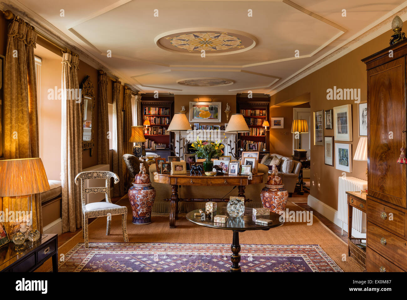 Elegant 1830's elm library table displaying lamps by William Yeoward in drawing room with bone inlay chair - Stock Image
