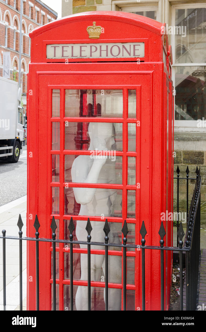 Red telephone box with fullsize statue of a man inside in St Giles' Square, Northampton - Stock Image