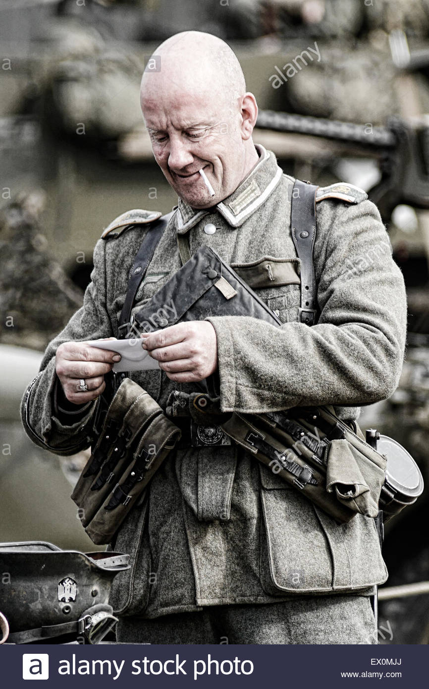 Re-enactor dressed as German WW2 soldier reading mail - Stock Image