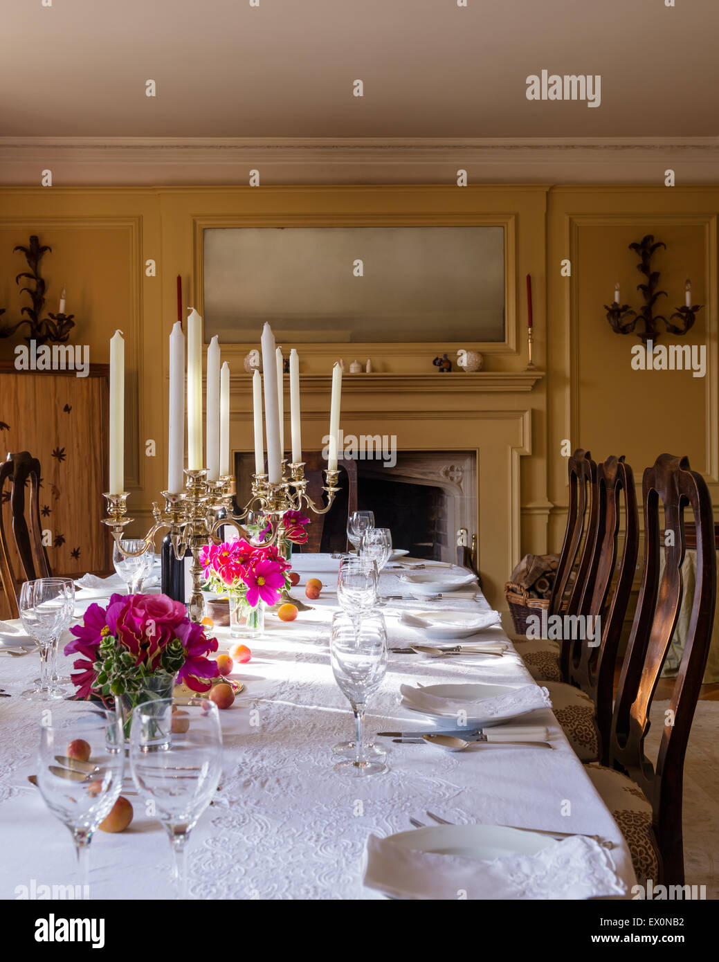 Candelabra on dining table with white cotton tablecloth and antique dining chairs - Stock Image