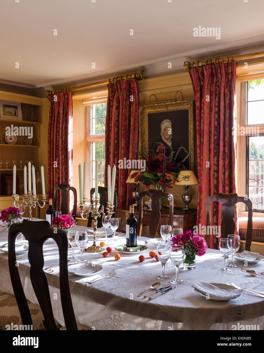 Gilt Framed Portait On Wall Of Dining Room With Candelabra And Floor Length Red Patterned Curtains