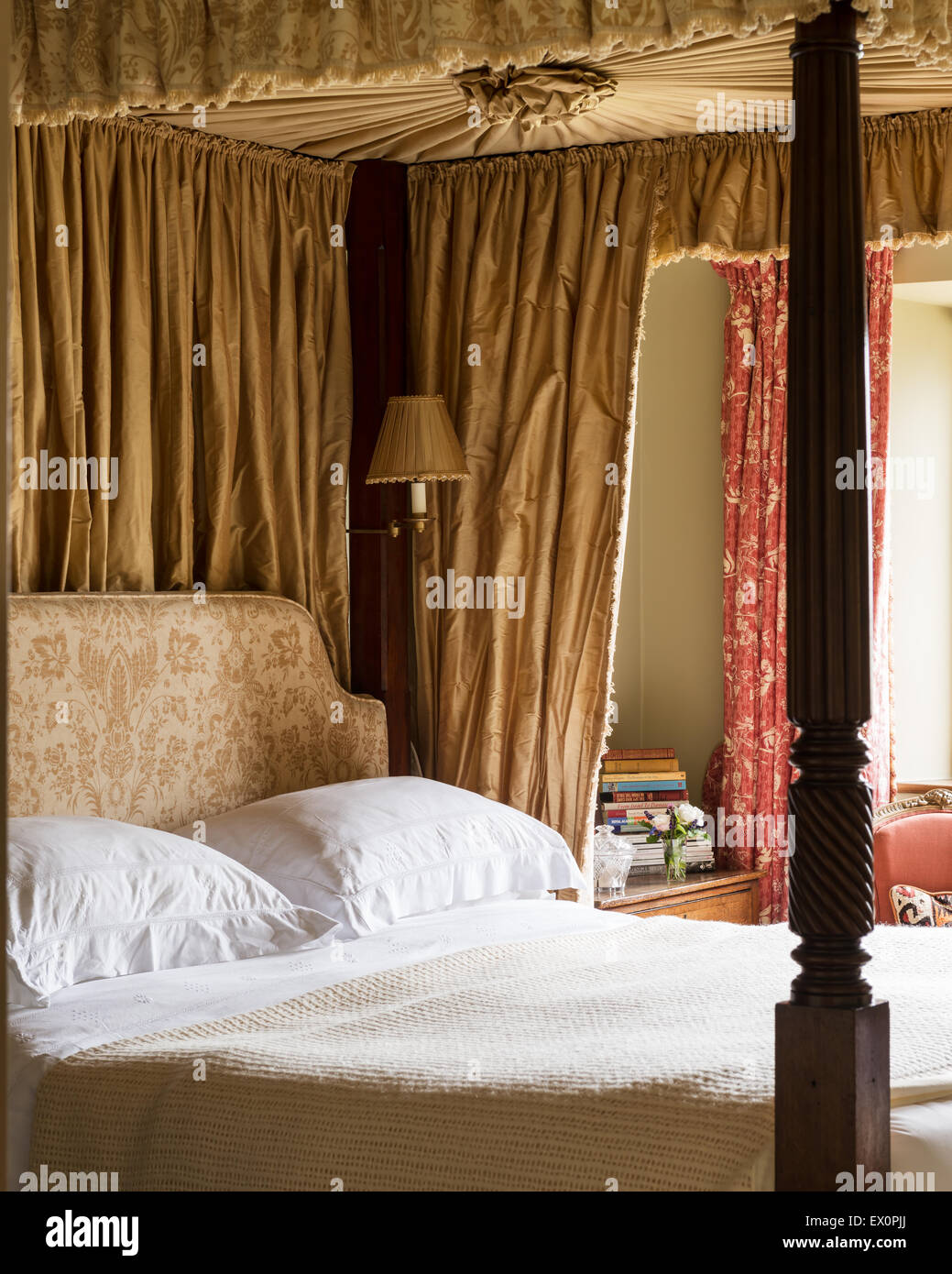 Georgian four poster bed in bedroom with toile de jouy curtains Stock Photo