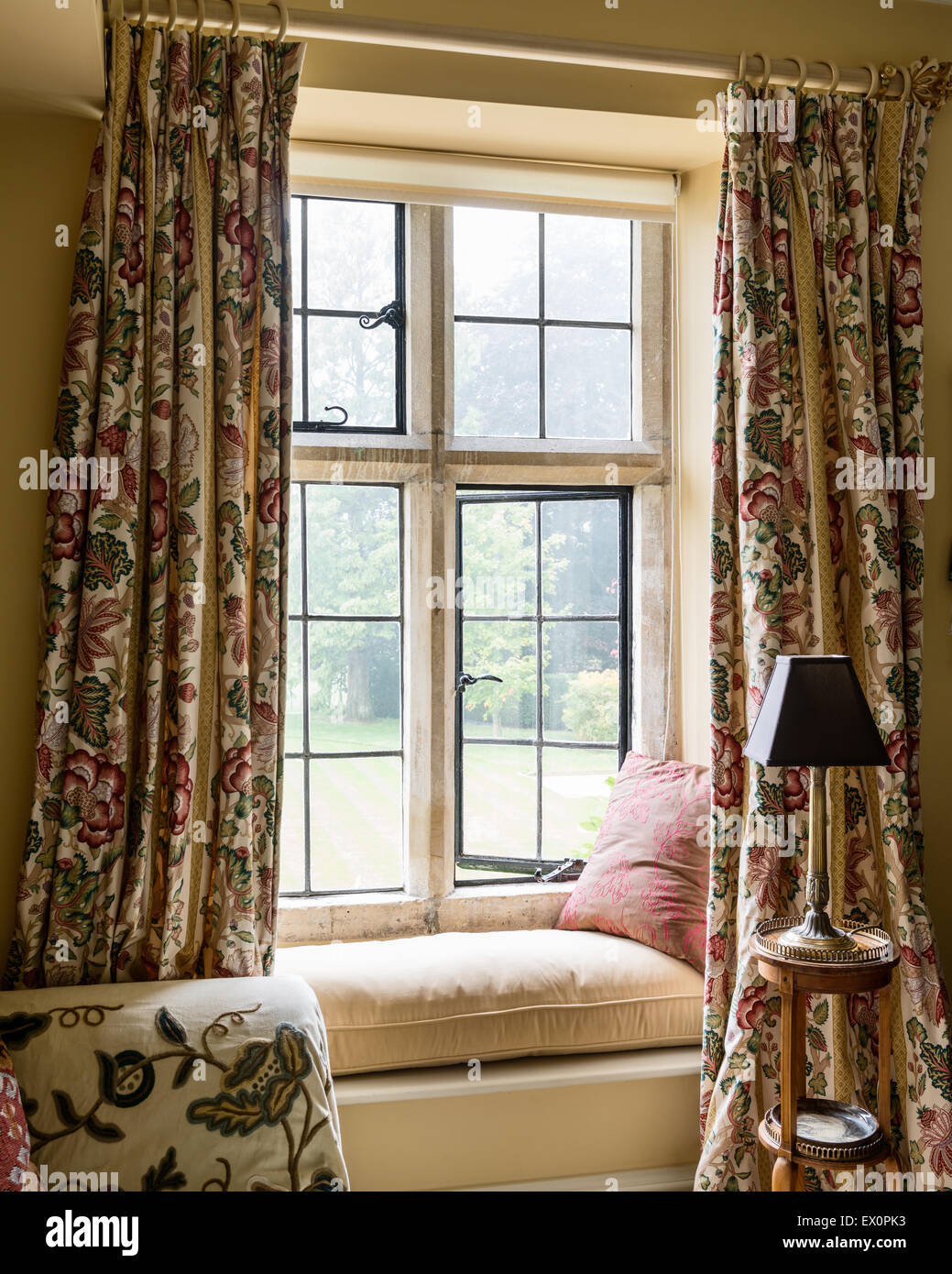 Floor length patterned curtains flanking window seat - Stock Image