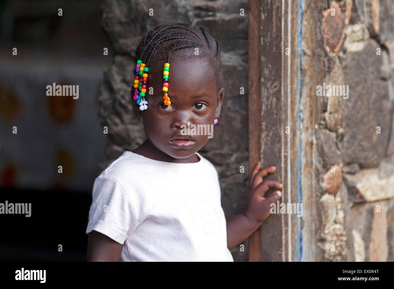 Creole girl with braided hair decorated with colourful beads in the village Rebelados on the island Santiago, Cape - Stock Image