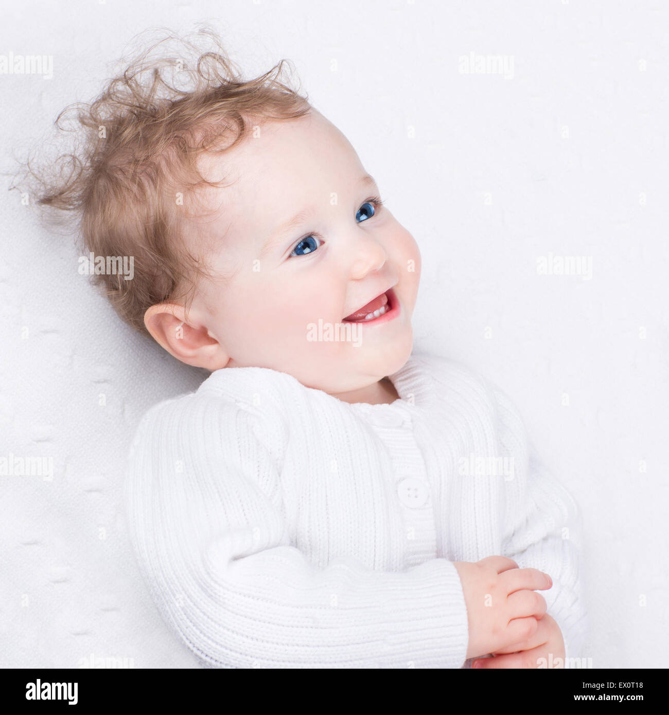 Adorable laughing little baby wearing a warm knitted jacket on a white blanket - Stock Image