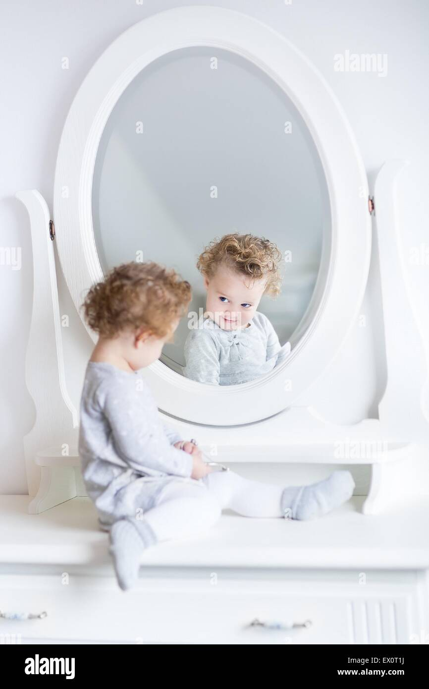 Funny cute baby girl watching her reflection in a white bedroom with a beautiful round mirror - Stock Image