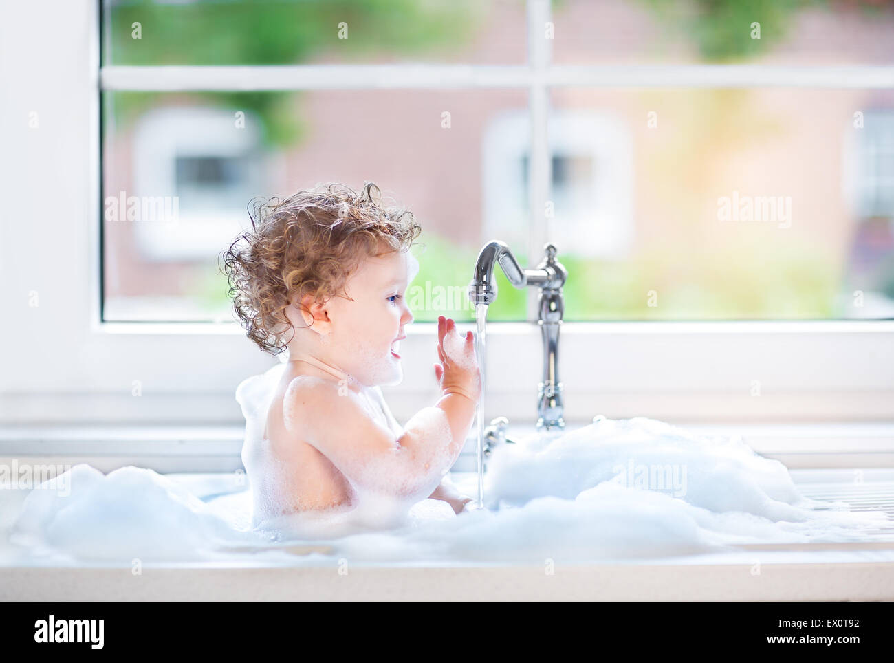 Funny happy baby girl playing in a kitchen sink full with foam next to a window - Stock Image