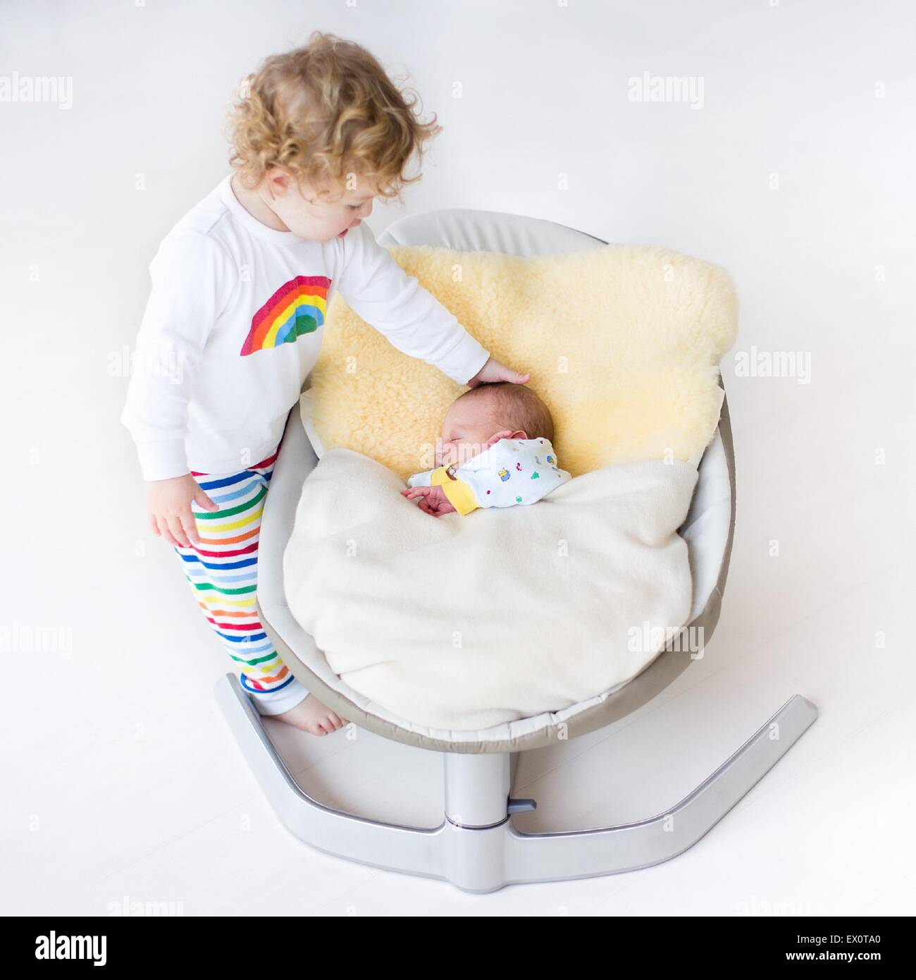 Tiny Newborn Baby Sleeping In A Swing On A Sheepskin With