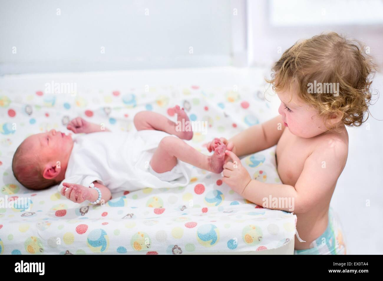 Portrait of a cute curly toddler girl playing with the feet of her newborn baby brother on a changing table - Stock Image