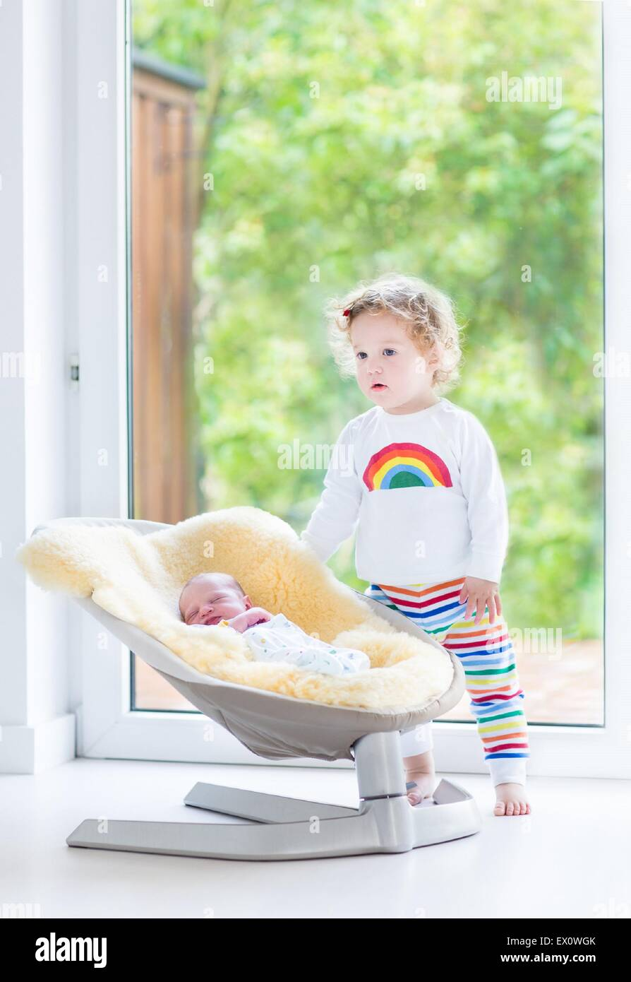Cute toddler girl playing with her newborn baby brother relaxing in a swing next to a big window and door to the - Stock Image