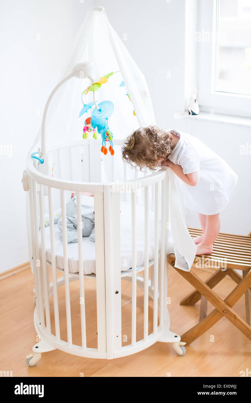 Funny curly toddler girl looking at her newborn baby brother sleeping in a white round crib with colorful toys and - Stock Image