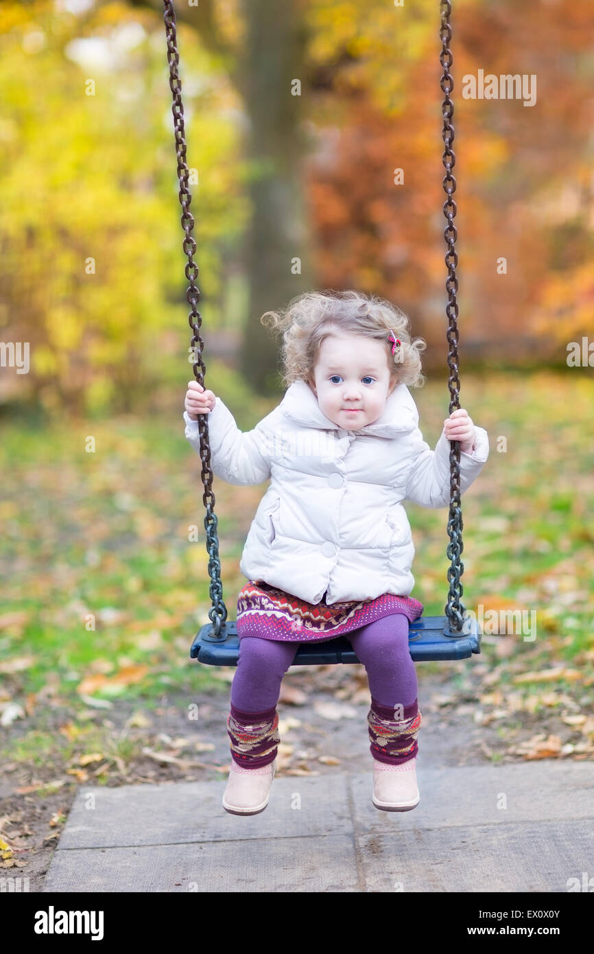 cute baby girl playing on a swing with beautiful autumn trees stock