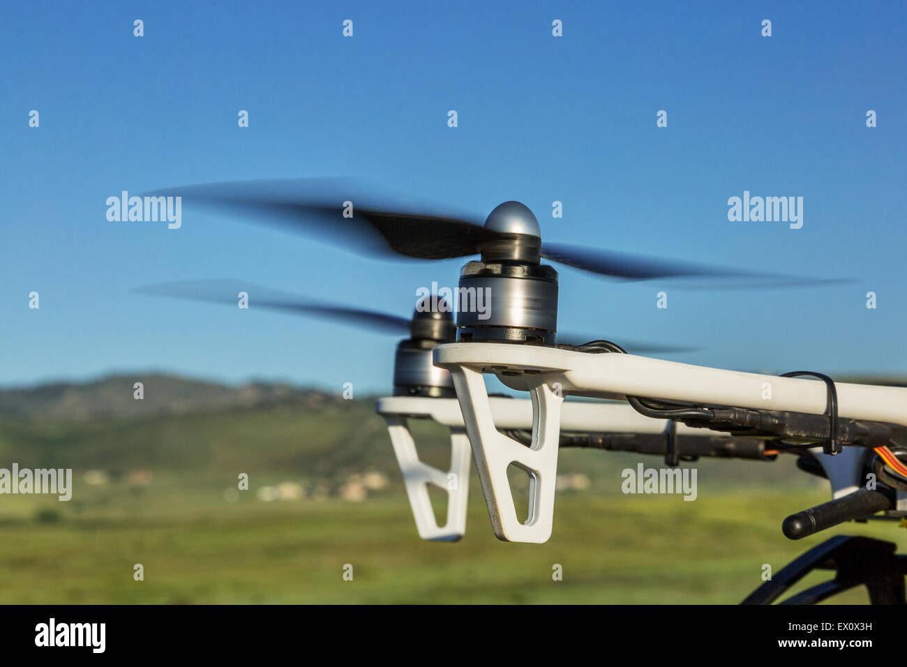 blurred spinning propellers of a hexacopter drone flying over foothills prairie - Stock Image