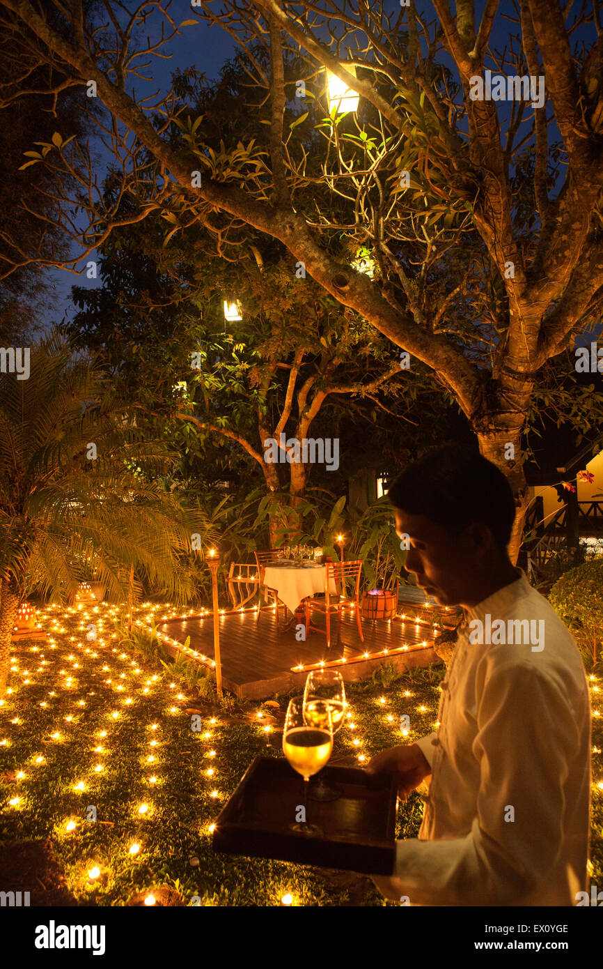 A special 500 Candle Dinner with waiter at dusk. La Residence Phou Vao hotel. Luang Prabang, Laos. - Stock Image