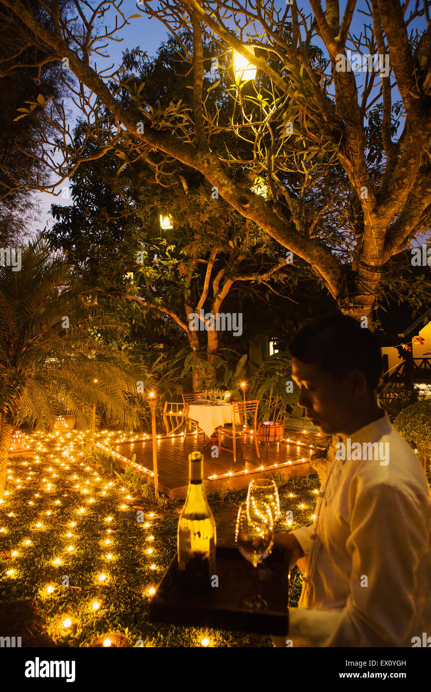 A special 500 Candel Dinner with waiter at dusk. La Residence Phou Vao hotel. Luang Prabang, Laos - Stock Image