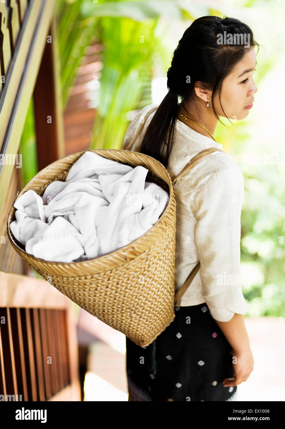 A chamber maid carries room towels in a basket on her back at 3 Nagas by Alila Hotel. Luang Prabang, Laos. - Stock Image